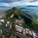 Molnigt grönt berg i staden Arkivfoton