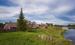Molnigt väder för sommar landskap med River Valley och det typiska byhuset i bygden Det gamla lantbrukarhemmet Royaltyfria Bilder