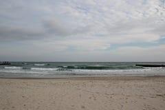 Molnigt väder Guld- sand, vågor och skum Molnig dag på den sandiga stranden Panoramautsikt av den härliga sandiga stranden Royaltyfri Bild