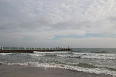 Molnigt väder Guld- sand, vågor och skum Molnig dag på den sandiga stranden Panoramautsikt av den härliga sandiga stranden Arkivbild