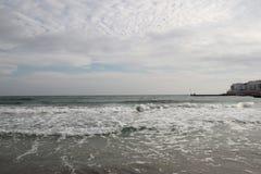 Molnigt väder Guld- sand, vågor och skum Molnig dag på den sandiga stranden Panoramautsikt av den härliga sandiga stranden Arkivbilder