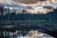 Molnreflexion på sjön på golfbanan med bron arkivfoto