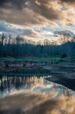 Molnreflexion på sjön på golfbanan med bron royaltyfri fotografi