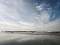 Molnreflexion på stranden arkivfoto
