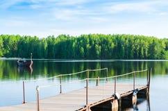 Molo da un lago della foresta con un peschereccio ancorato Immagini Stock Libere da Diritti