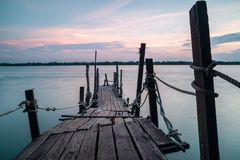 Molo di legno fuori al mare durante il tramonto fotografia stock libera da diritti