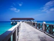 Molo di legno in mezzogiorno sotto i chiari cieli blu con la camminata della gente fotografie stock libere da diritti