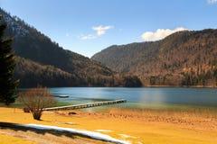 Molo di legno nel lago Alpsee con le montagne delle alpi nei precedenti La Baviera, Germania Immagini Stock