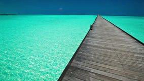 Molo lungo di legno sopra la laguna in Maldive con acqua pulita stock footage