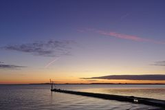 Molo przed wschodem słońca z mały dźwigowy sylwetkowym przeciw ranku nieba i czerwień opary śladu koszt stały Obraz Stock