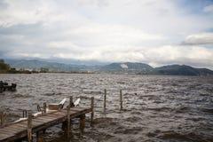 Molo sul lago, sulle acque di difficoltà e sul vento Immagini Stock Libere da Diritti