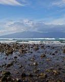 Molokai. Waves furl up near a rocky beach in front of the island of Molokai Stock Photos