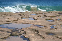 Molokai Hawaii Tide Pools. Tide pools in sandstone rock along the west coast of the tropical island of Molokai Hawaii with a wave about to wash ashore stock images