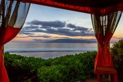 Molokai Island at Sunrise. Sunrise on Molokai Island under a cabana at Maui, Hawaii Stock Photos