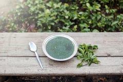 Molokhia, grüne Suppe in der silbernen Schüssel auf Holztisch Lizenzfreie Stockfotos