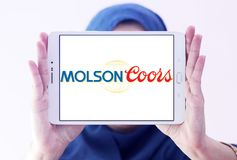Molson Coors Brewing Company logo. Logo of Molson Coors Brewing Company on samsung tablet holded by arab muslim woman Royalty Free Stock Image