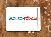 Molson Coors Brewing Company logo. Logo of Molson Coors Brewing Company on samsung tablet on wooden background Stock Image