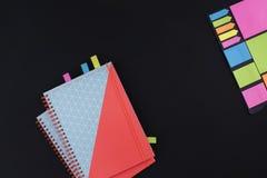 Molta carta colorata differente per la scrittura del taccuino per una scuola su un fondo nero Concetto dell'ufficio Copi lo spazi Fotografie Stock