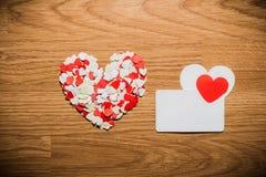 Molta carta rossa e bianca di nome e del cuore su un fondo di legno Fotografie Stock