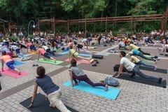 Molta gente è impegnata nell'yoga nel parco della dinamo il giorno internazionale di yoga Immagini Stock