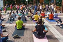 Molta gente è impegnata nell'yoga nel parco della dinamo il giorno internazionale di yoga in Voronež, Russia Fotografia Stock