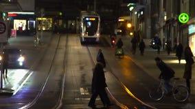 Molta gente attivamente che muove intorno la città facendo uso di vari veicoli, ora di punta di notte archivi video