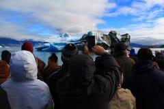 Molta gente che guarda e che fotografa un iceberg Fotografie Stock