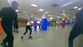 Molta gente dei bambini e degli adulti va pattinare sul rollerdrom video d archivio