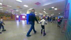 Molta gente dei bambini e degli adulti va pattinare sul rollerdrom stock footage