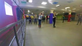 Molta gente dei bambini e degli adulti va pattinare sul rollerdrom archivi video