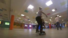 Molta gente dei bambini e degli adulti va pattinare sul rollerdrom interno archivi video