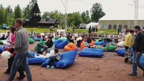 Molta gente si trova sui beanbags enormi sulla sabbia in parco Festival di estate pubblici stock footage