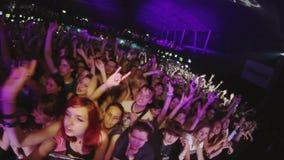Molta gente solleva le mani sul concerto rock in tensione in night-club ammucchiato riflettori eccitamento archivi video