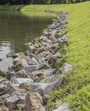 Molta roccia sulla riva vicino al lago Fotografie Stock