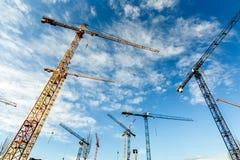 Molte alte gru a torre lavorano ad una costruzione di nuovi edifici Fotografie Stock