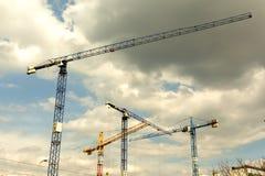 Molte alte gru a torre lavorano alla costruzione di nuove case Immagini Stock