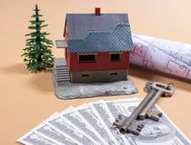 Molte banconote del dollaro, la chiave e una casa modellano Concetto di acquisto della casa Immagini Stock