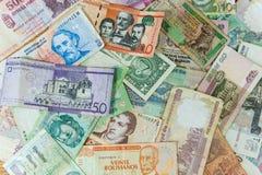 Molte banconote internazionali sparse sulla tavola fotografie stock