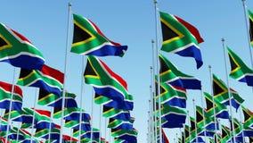 Molte bandiere sudafricane che ondeggiano nel vento contro il chiaro cielo blu illustrazione vettoriale