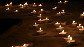 Molte belle, candele bianche rotonde e piccole che bruciano nella sabbia nello scuro archivi video