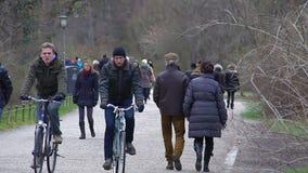 Molte biciclette di guida della gente e camminare nel parco della città, godente dell'aria fresca della molla stock footage