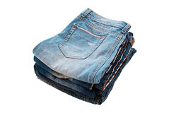 Molte blue jeans sul bianco Immagini Stock