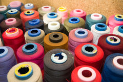 Molte bobine dei fili che stanno sulla tavola Fotografia Stock