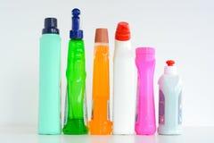 Molte bottiglie delle soluzioni di pulizia isolate su fondo bianco Fotografie Stock