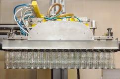 Molte bottiglie di vetro che appendono in una pinza di presa pneumatica Bottiglie di vetro di carico dai pallet fotografie stock