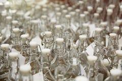 Molte bottiglie di vetro trasparenti con le spine bianche Immagine Stock Libera da Diritti