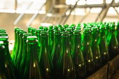Molte bottiglie sul nastro trasportatore immagini stock