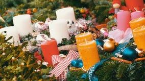 Molte candele spesse della cera grande di Natale colorato multi che stanno nell'agrifoglio e nell'abete rosso Lo spirito del Nata stock footage