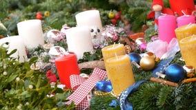 Molte candele spesse della cera grande di Natale colorato multi che stanno nell'agrifoglio e nell'abete rosso Lo spirito del Nata video d archivio