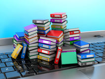 Molte cartelle variopinte impilate in una fila su un computer portatile Fotografie Stock Libere da Diritti